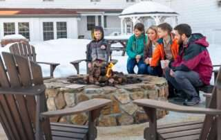 family sitting around fire pit